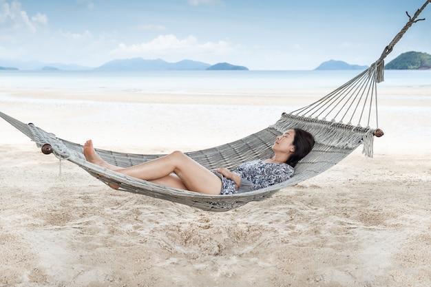 Bella donna che dorme sull'amaca sulla spiaggia, momento dalla vocazione.