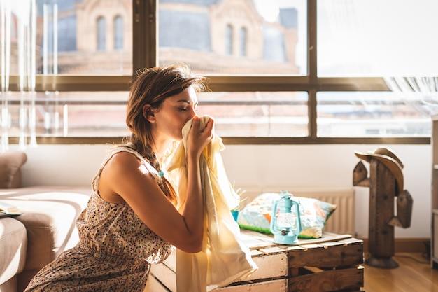 Bella donna sentente l'odore di vestire a casa.