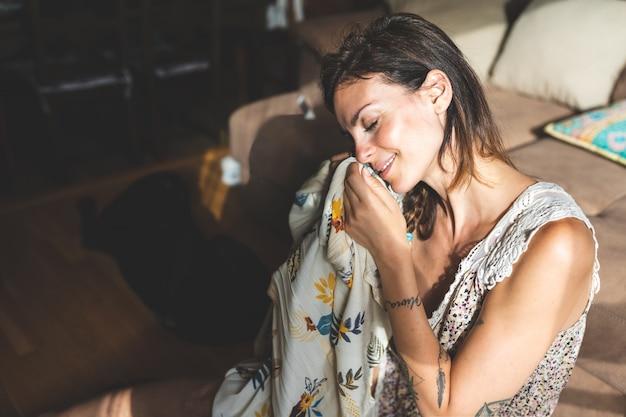 Bella donna che sente l'odore dei suoi vestiti a casa