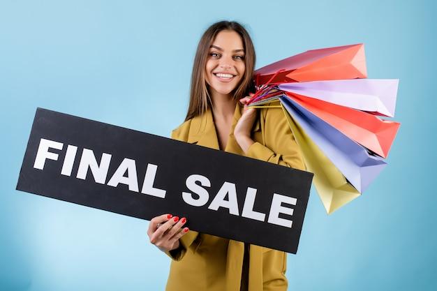 Bella donna che sorride tenendo l'insegna nera di vendita finale e i sacchetti della spesa variopinti