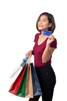 Bella donna sorridente tenendo i sacchetti della spesa con carta di credito isolato su bianco