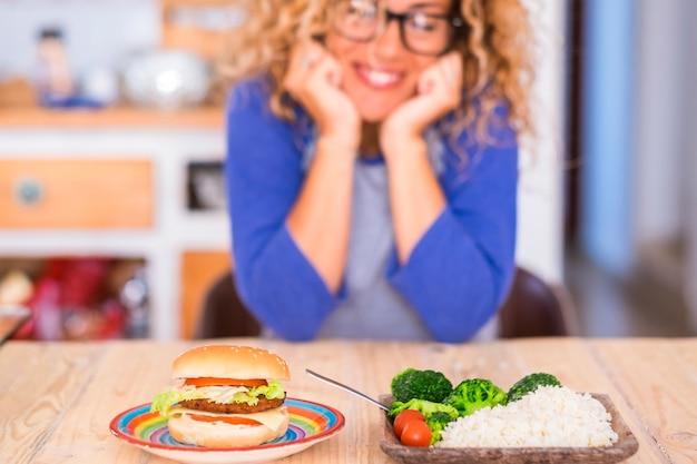 Bella donna che sorride e guarda il tavolo - scegliendo hamburger o riso e verdure - concetto di stile di vita sano e salutare