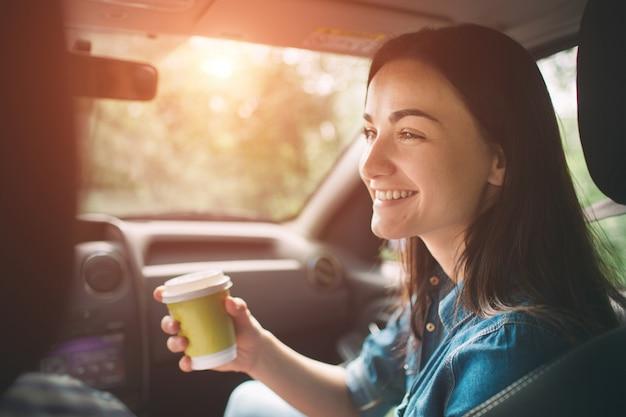 Bella donna che sorride mentre sedendosi sui sedili del passeggero anteriore in macchina e lei sta bevendo il caffè da una tazza usa e getta