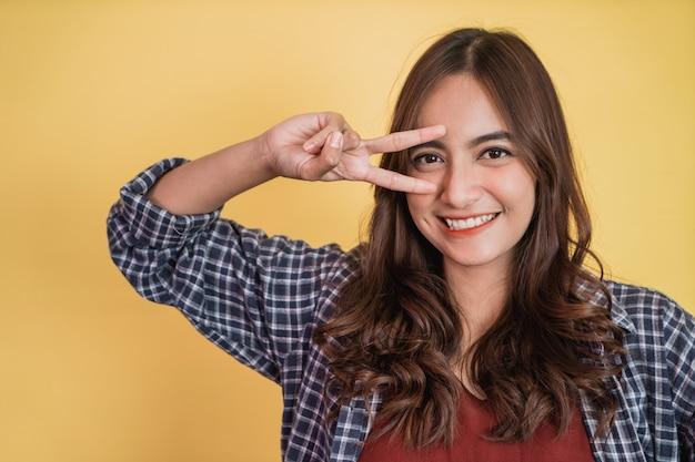 Bella donna sorridente con pace che fa un gesto con due dita davanti ai suoi occhi