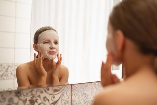 Una bella donna leviga, mette sul viso una maschera cosmetica in bagno davanti allo specchio