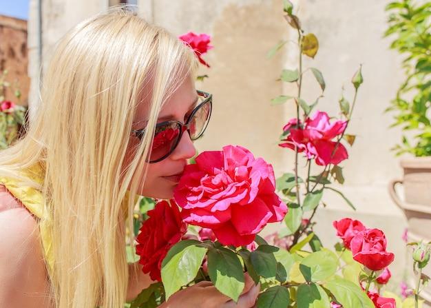 La bella donna annusa le rose rosse fragranti nel giardino.
