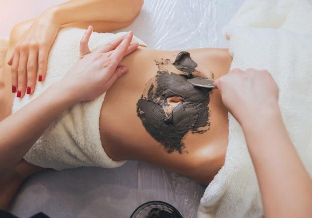 Bella donna nel salone della stazione termale che ottiene massaggio del corpo del fango
