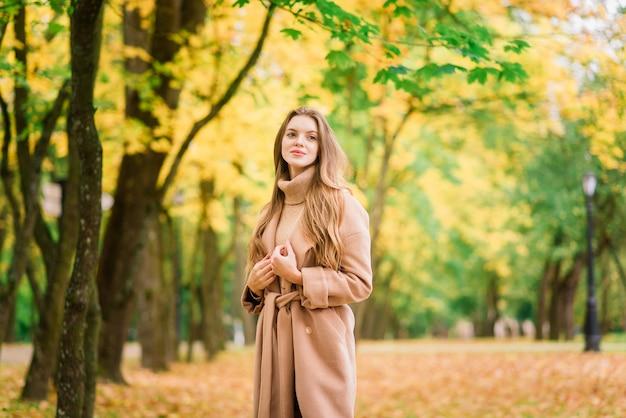 Bella donna di trascorrere del tempo in un parco durante la stagione autunnale