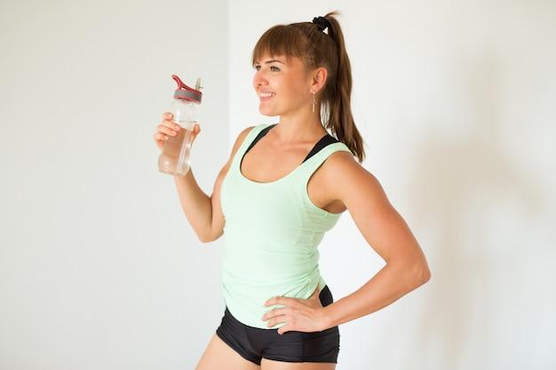 Bella donna in abiti sportivi con una bottiglia di acqua