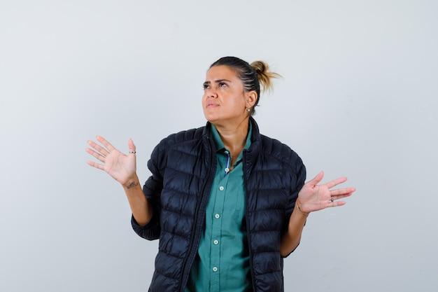 Bella donna che allarga le palme da parte in modo incapace in camicia verde, giacca nera e sembra pensierosa, vista frontale.