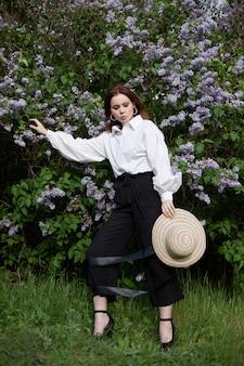 Bella donna in primavera tra i rami dei cespugli fioriti di lilla ritratto di una donna in una luminosa giornata estiva