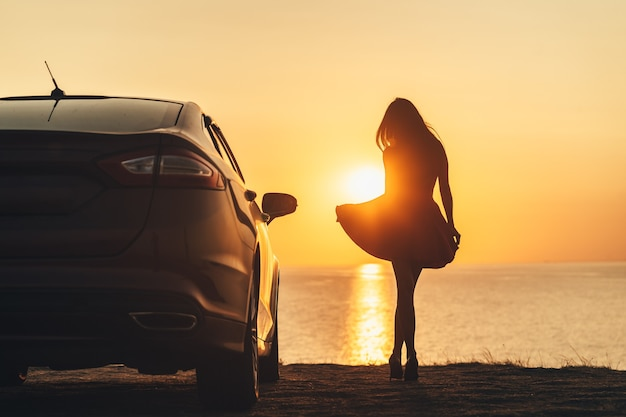 La bella donna in piedi vicino alla macchina in riva al mare