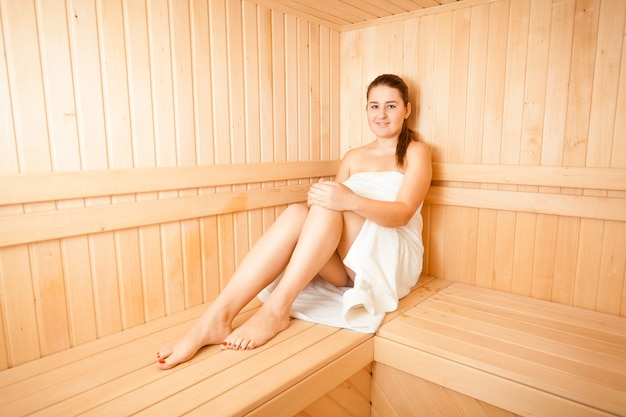 Bella donna che fuma nella sauna