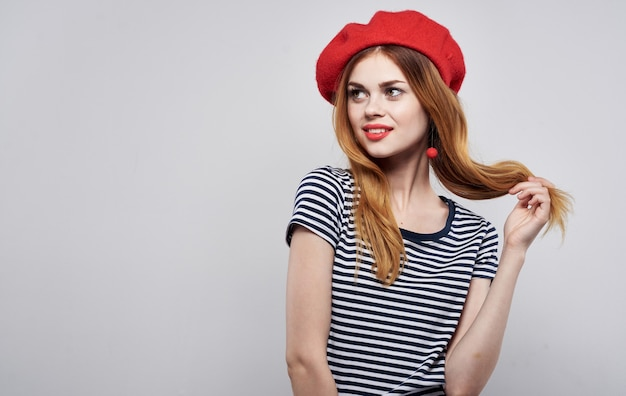 La bella donna in un gesto delle labbra rosse della maglietta a strisce con le sue mani ha isolato il fondo