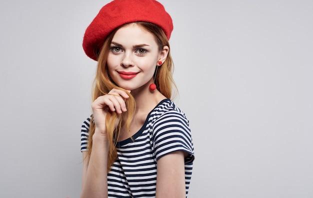 Bella donna in un gesto di labbra rosse maglietta a righe con le sue mani sfondo chiaro