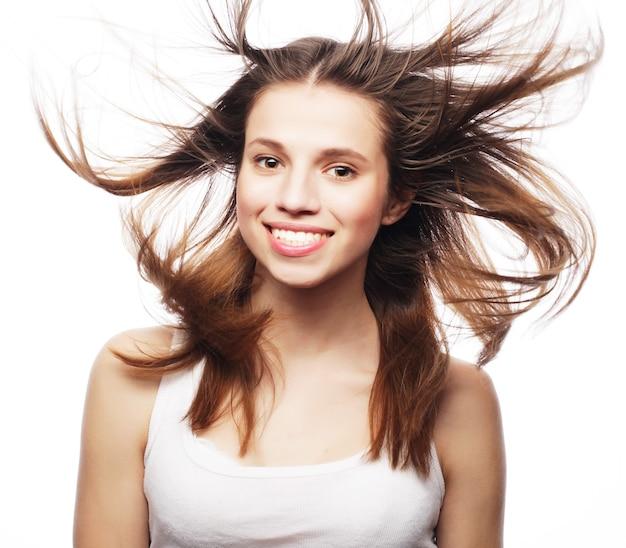 Bella donna in studio girato con vento sui capelli.