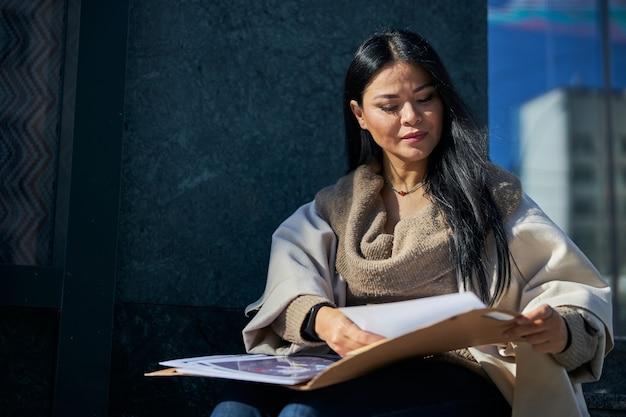 Bella donna che studia i documenti per strada