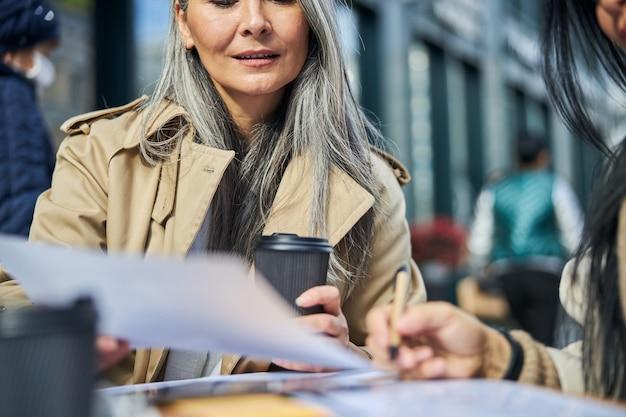 Bella donna che studia documenti con un collega all'aperto