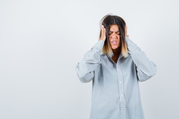 Bella donna che soffre di forte mal di testa in camicia e sembra angosciata, vista frontale.