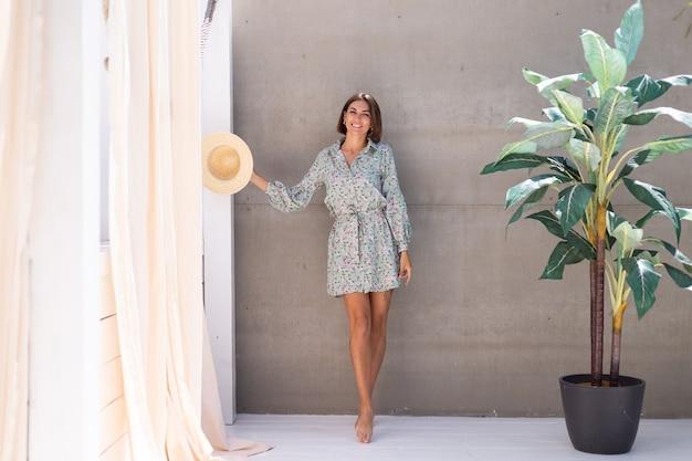 Bella donna in abito estivo e cappello di paglia vicino alla palma e al muro grigio