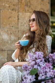 Bella donna in occhiali da sole godersi il caffè del mattino vicino al fiore lilla. modello carino e fiori. aromaterapia e concetto di primavera. la ragazza beve il caffè alla caffetteria.