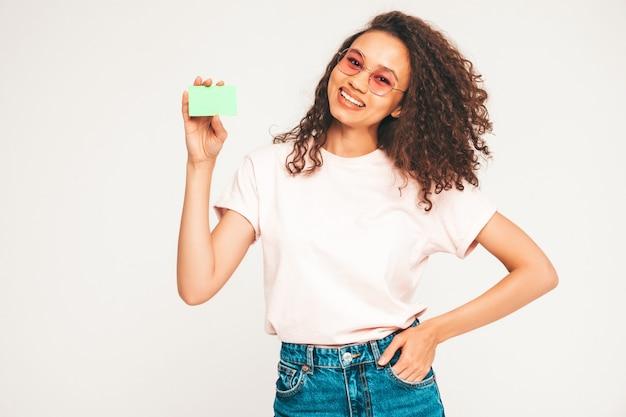 Bella donna in occhiali da sole che mostra carta di credito verde