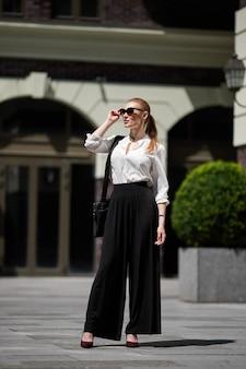 Bella donna in occhiali da sole in strada
