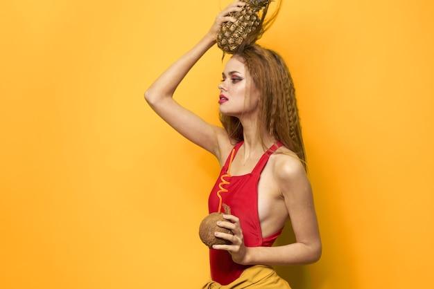 Bella donna in costume da bagno, costume da bagno rosso, immagine divertente con cocco frutti tropicali e ananas