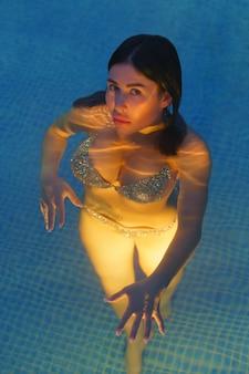 Bella donna in costume da bagno che nuota in acqua in piscina presso la stazione termale geotermica. foto al tramonto, il corpo sinuoso della donna è illuminato sott'acqua dalle luci notturne in piscina. soggiorno medico presso resort di balneoterapia.