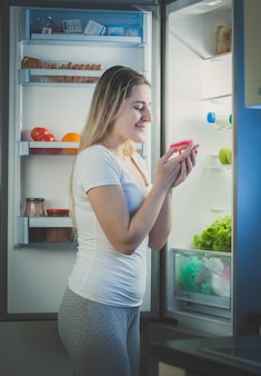 Bella donna che prende la ciambella dal frigo a tarda sera