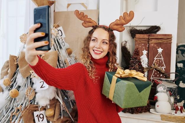 Bella donna che cattura selfie con presente