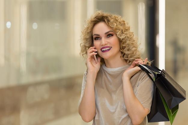 Bella donna che parla al telefono con le borse al centro commerciale.