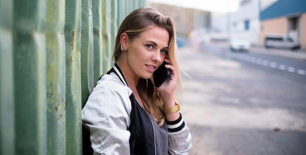 Bella donna o adolescente che parla con il suo ragazzo o i suoi amici con il suo telefono in una strada urbana guardando l'orizzonte
