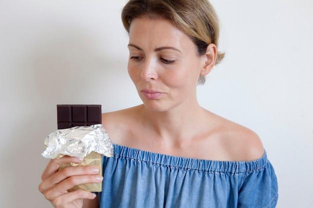Ritratto di una giovane bella ragazza con i capelli biondi, spalle nude e un collo, che tiene in mano una barretta di cioccolato per godersela.