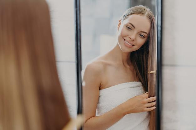 Bella donna in asciugamano spazzolarsi i capelli