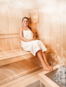 Bella donna in asciugamano rilassante sulla panchina nella sauna al vapore
