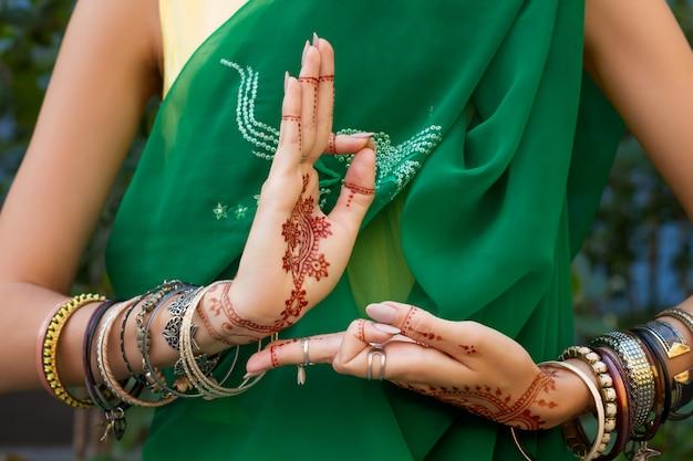 Bella donna in costume tradizionale indiano musulmano verde abito da sari costume con gioielli tatuaggio henné e bracciali fare le mani nritta odissi samyuta hastas danza movimento araala concetto sfondo