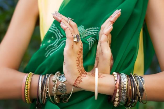 La bella donna in sari verdi musulmani indiani tradizionali si veste di mani con gioielli e bracciali per tatuaggi all'henné fa ballare nritta odissi samyuta hastas. movimento nagabanda coppia di serpenti