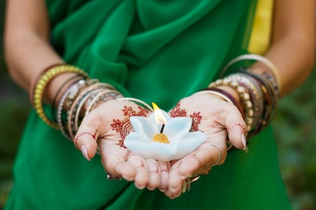 Bella donna nel tradizionale matrimonio indiano musulmano verde sari abito mani con tatuaggio all'henné mehndi modello gioielli e bracciali tenere bruciando candela di loto cultura estiva festival celebrazione concetto