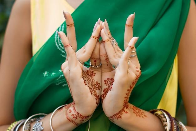 Bella donna in abito da sari verde tradizionale indiano musulmano da sposa con bracciali gioielli con tatuaggi all'henné mani nritta odissi samyuta hasta mudras danza movimento bocciolo di loto fiore concetto sfondo