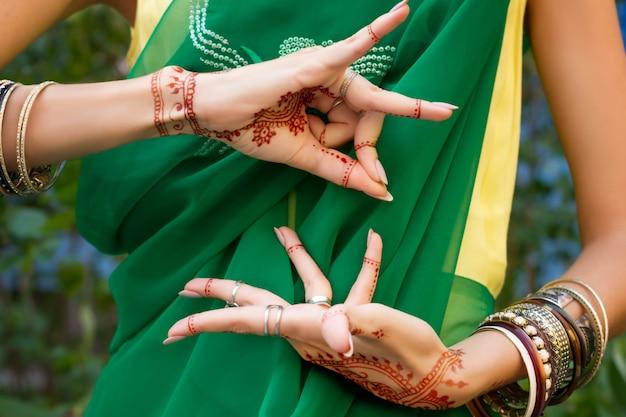 Bella donna in abito da sari verde tradizionale indiano musulmano da sposa con gioielli e bracciali tatuaggio all'henné mani nritta odissi samyuta hastas danza movimento alapadma bramara concetto sfondo
