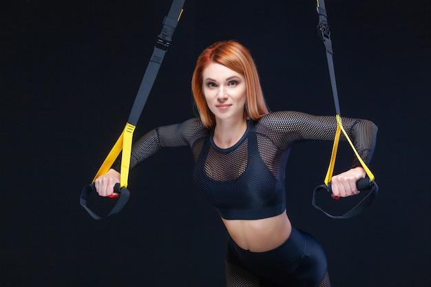 Bella donna allenamento con cinghie di fitness