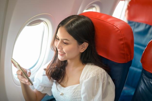La bella donna che viaggia sta usando lo smartphone sull'aereo