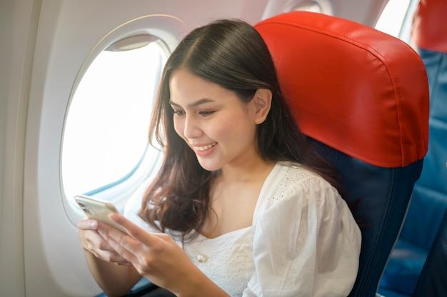 Il viaggiatore della bella donna sta usando lo smartphone sull'aeroplano