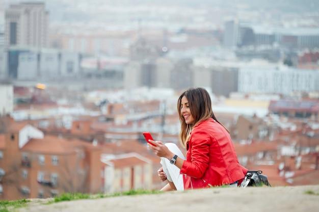 Una bella donna che utilizza il cellulare con la città