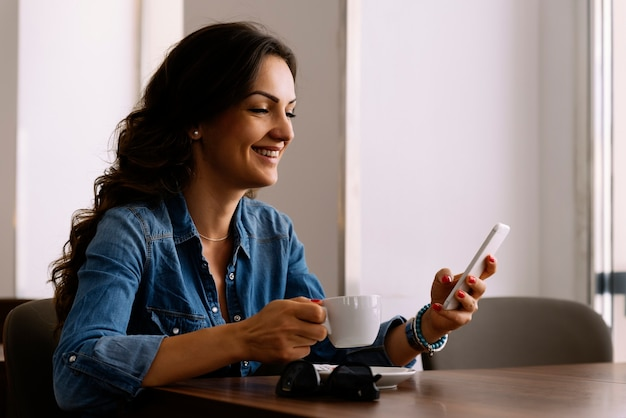 Bella donna che usa il suo cellulare nella caffetteria.
