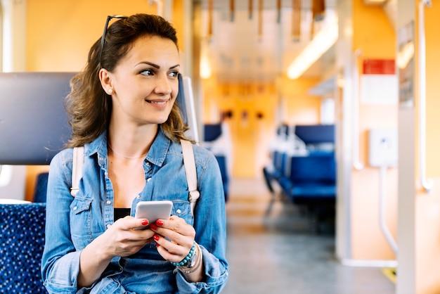 Bella donna che usa il suo cellulare in treno.