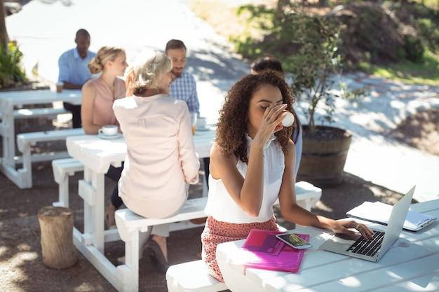 Bella donna che per mezzo del computer portatile mentre beve il caffè
