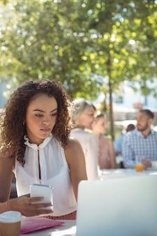 Bella donna che per mezzo del telefono cellulare e del computer portatile