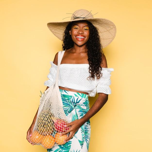 Bella donna che usa una borsa a rete quando compra la frutta